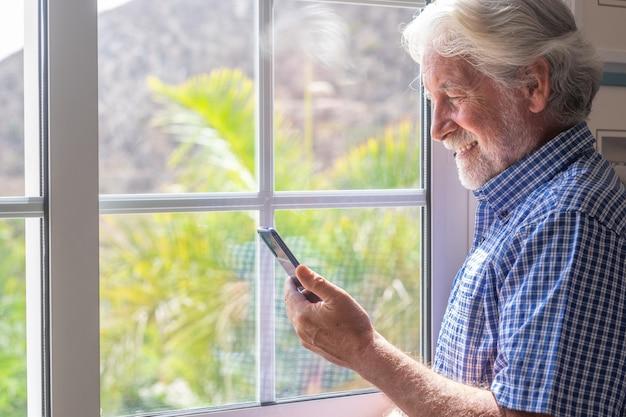 Glimlachende senior man bij het raam kijken naar mobiele telefoon