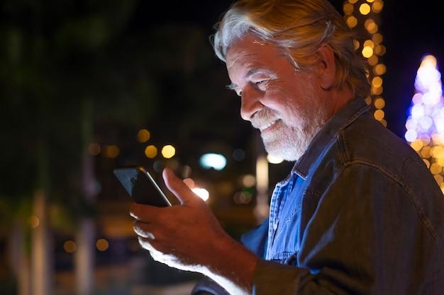Glimlachende senior man buiten in de nacht kijkend naar zijn smartphone met kerstboom en verlichting op de achtergrond