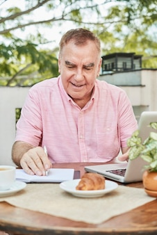 Glimlachende senior man die gegevens in de planner controleert wanneer hij 's ochtends op een laptop op een terras werkt
