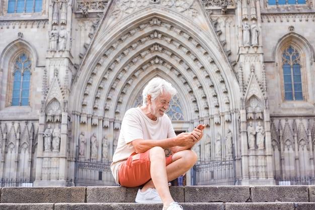Glimlachende senior man die geniet van een bezoek aan de kathedraal van barcelona, zittend op de trap met mobiele telefoon