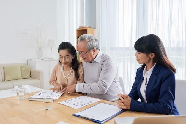 Glimlachende senior man en vrouw ontmoeten een makelaar in onroerend goed en kijken en bouwen plannen wanneer ko...