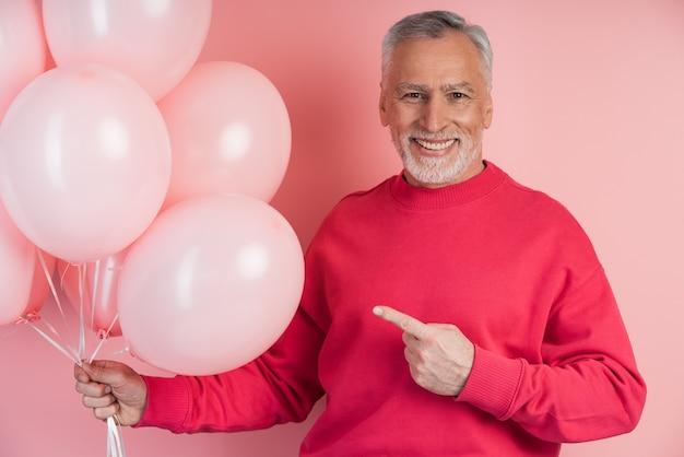 Glimlachende senior man met ballonnen op een roze muur, wijzend naar hen met zijn vinger