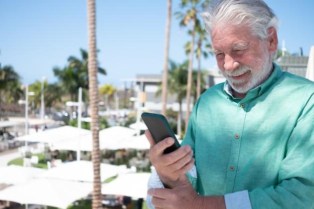 Glimlachende senior man met behulp van mobiele telefoon buiten tijdens een zonnige dag. aantrekkelijke witharige gepensioneerden die genieten van technologie en sociale media