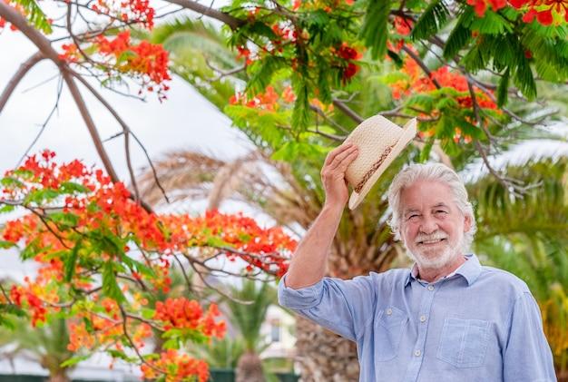 Glimlachende senior man met strohoed staande in openbaar park dicht bij een rood bloeiende plant