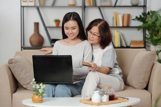 Glimlachende senior vietnamese vrouw die betaalt voor online aankopen van haar volwassen dochter wanneer ze samen thee drinken in de woonkamer