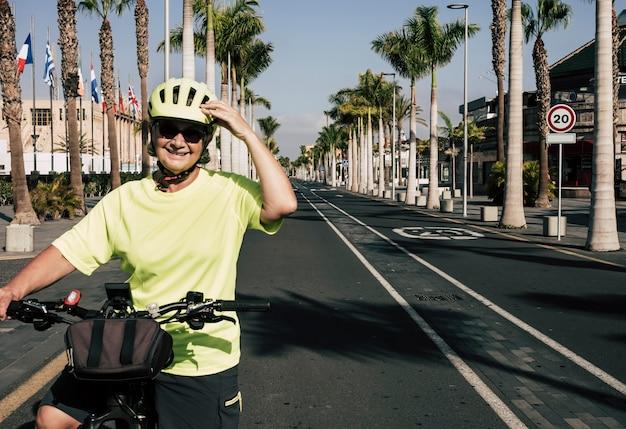 Glimlachende senior vrouw met gele helm en t-shirt fietsen in tenerife in de verlaten stad - toerismecrisis - nieuw normaal voor gepensioneerden