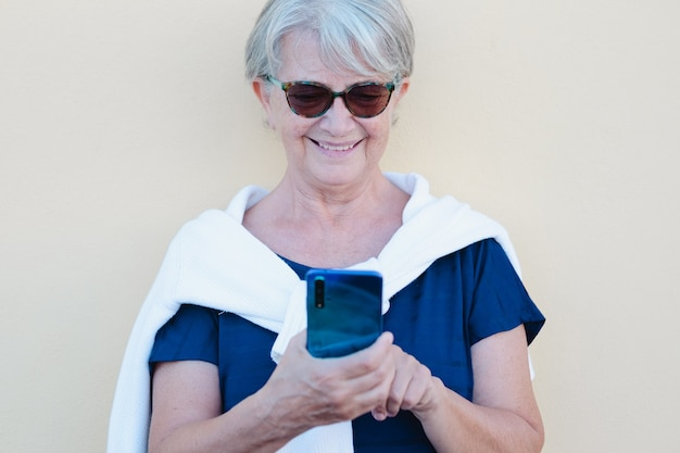 Glimlachende senior witharige vrouw met behulp van mobiele telefoon in video-oproep. serene gepensioneerden die buiten genieten van tech en sociaal