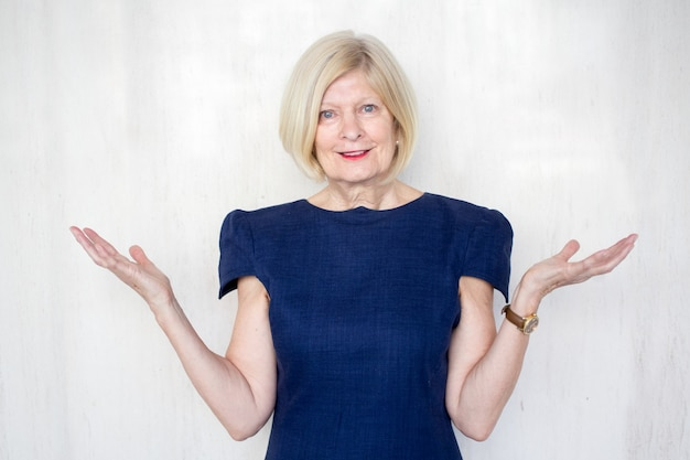 Glimlachende senior zakenvrouw shrugging schouders