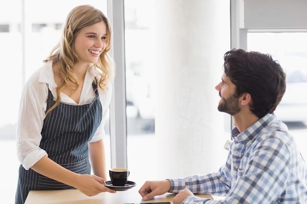 Glimlachende serveerster die een koffie dient aan klant