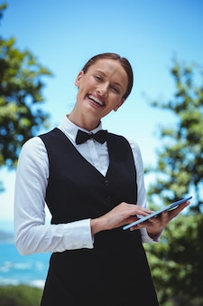 Glimlachende serveerster die een orde met een tablet neemt