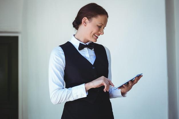 Glimlachende serveerster die een tablet gebruikt