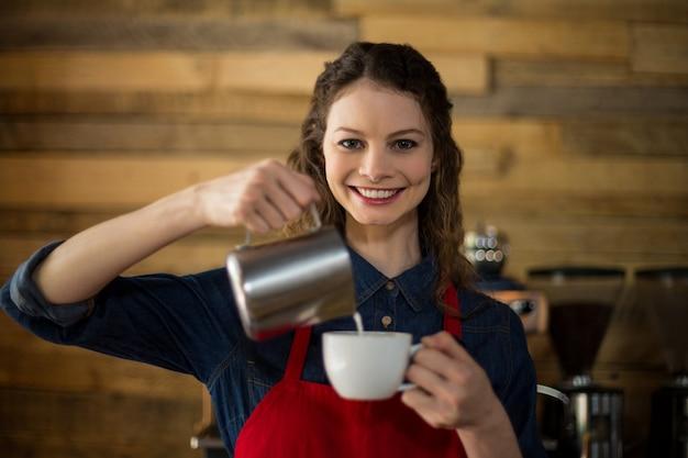 Glimlachende serveerster die kop van koffie maakt