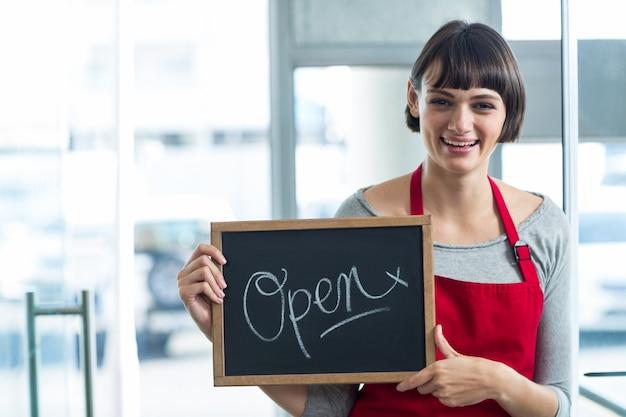 Glimlachende serveerster die lei met open teken toont