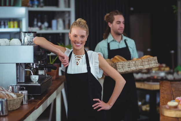 Glimlachende serveerster die zich achter de toonbank bevindt