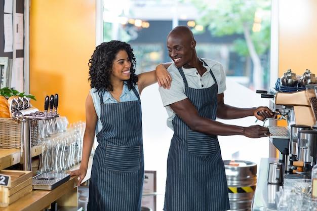 Glimlachende serveerster en ober die terwijl het werken bij teller op elkaar inwerken