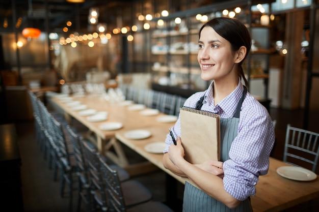 Glimlachende serveerster working in restaurant