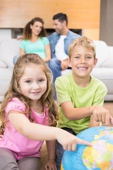 Glimlachende siblings die aan bol op de deken richten