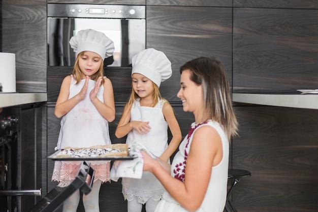 Glimlachende siblings die moeder bekijken die verse gebakken koekjes in dienblad houden