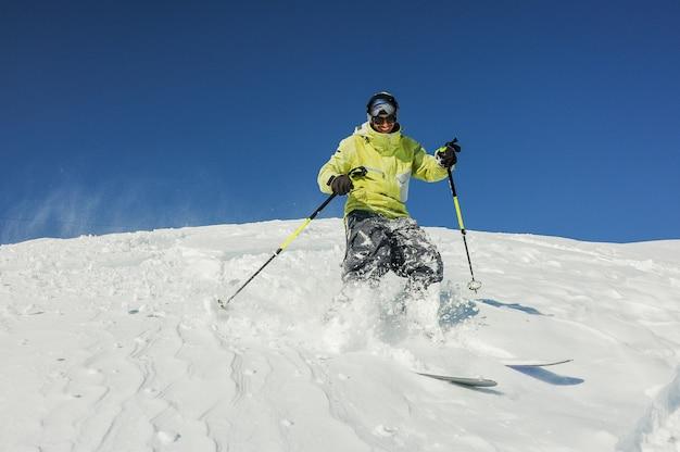 Glimlachende skiër in gele sportkleding die onderaan de helling in georgië, gudauri berijden