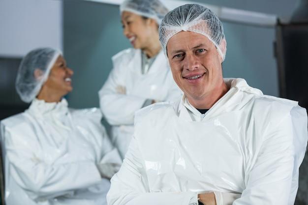 Glimlachende slager die zich met gekruiste wapens bevindt