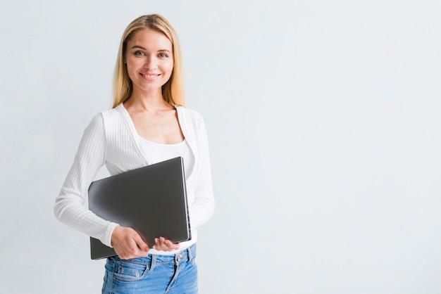 Glimlachende slanke blonde vrouw in jeans met zwarte laptop