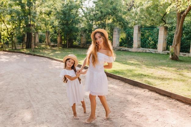 Glimlachende slanke dame in trendy witte jurk poseren in de buurt van dochtertje op straat met ijzeren hek. outdoor portret van schattig meisje en haar slanke moeder in hoed tijd doorbrengen in park.