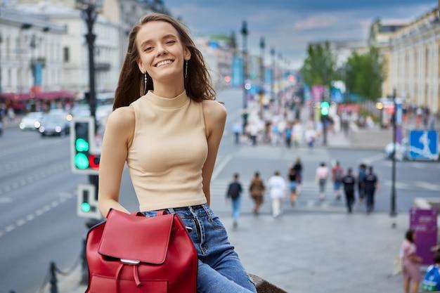 Glimlachende slanke europese vrouw jaar oud rust 's avonds op straat in de stad