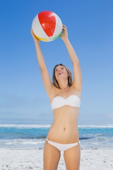 Glimlachende slanke vrouw die strandbal vangt