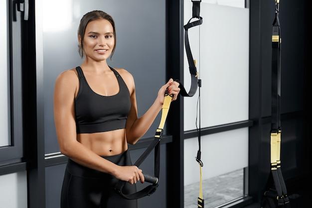 Glimlachende slanke vrouw die zich voorbereidt op training met trx