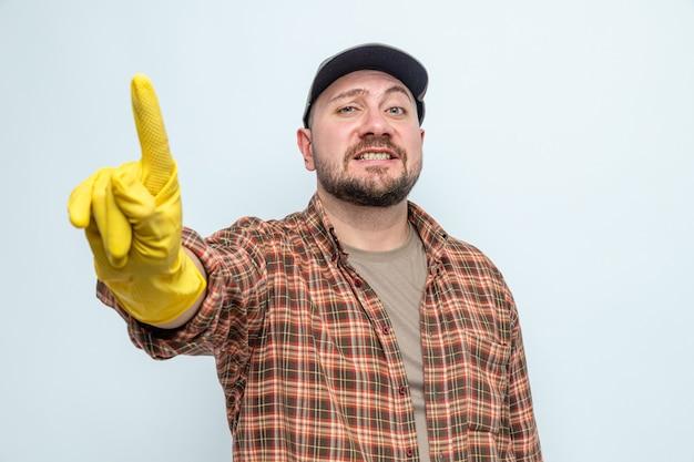 Glimlachende slavische schonere mens met rubberhandschoenen die zijn wijsvinger tonen