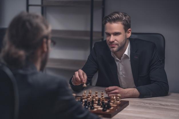 Glimlachende slimme jonge aantrekkelijke mens met in hand schaakstuk en tegenstander die in bureau speelt