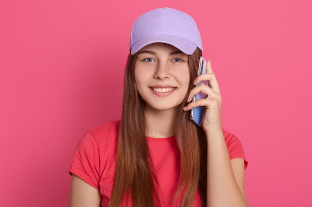 Glimlachende slimme telefoon houden dichtbij haar oor en vrouw die glimlachen die, rood toevallig t-shirt en honkbal glb dragen, zich tegen roze muur bevinden.