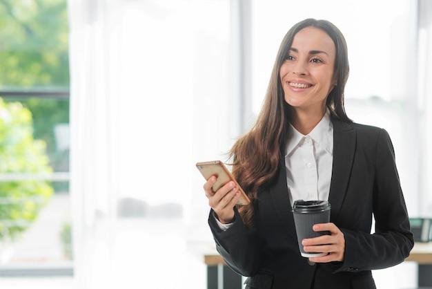 Glimlachende smartphone van de onderneemsterholding en beschikbare koffiekop