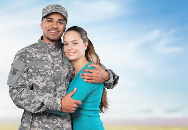 Glimlachende soldaat met zijn vrouw die tegen de achtergrond staat