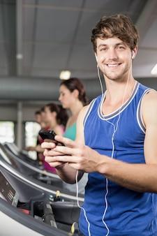 Glimlachende spiermens die op tredmolen aan muziek bij gymnastiek luisteren
