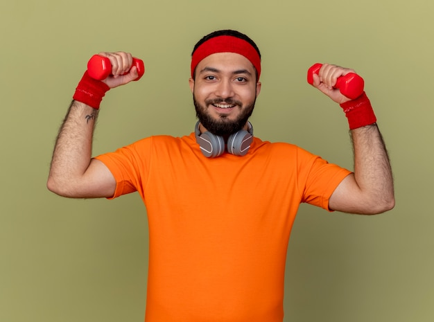 Glimlachende sportieve jongeman met hoofdband en polsband met koptelefoon op nek trainen met halters geïsoleerd op olijfgroene achtergrond
