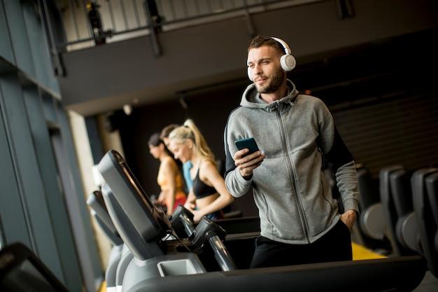 Glimlachende sportieve mens die aan muziek in gymnastiek luistert