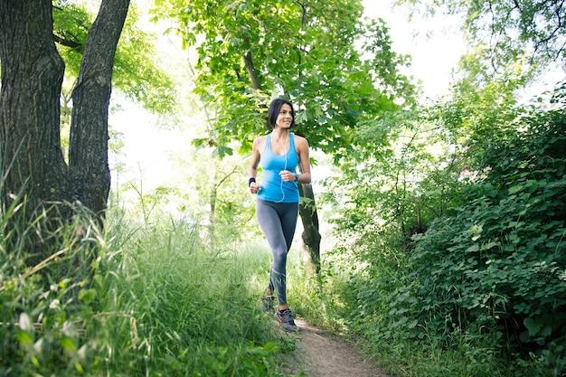 Glimlachende sportieve vrouw die buiten loopt