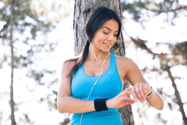 Glimlachende sportieve vrouw die slim horloge met behulp van