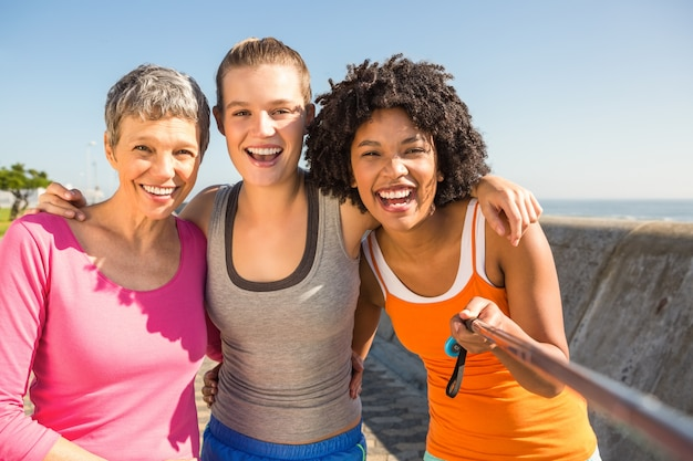 Glimlachende sportieve vrouwen die selfies met selfiestick nemen