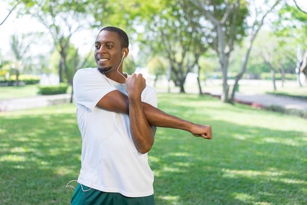 Glimlachende sportieve zwarte mens die aan muziek luisteren en ochtendoefeningen in park doen.