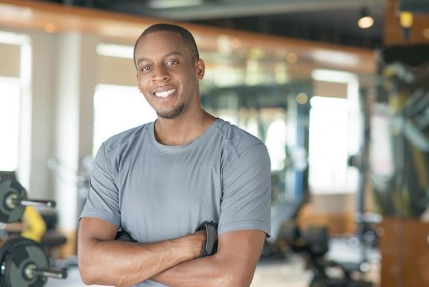 Glimlachende sportieve zwarte mens die zich met zijn gekruiste wapens bevindt