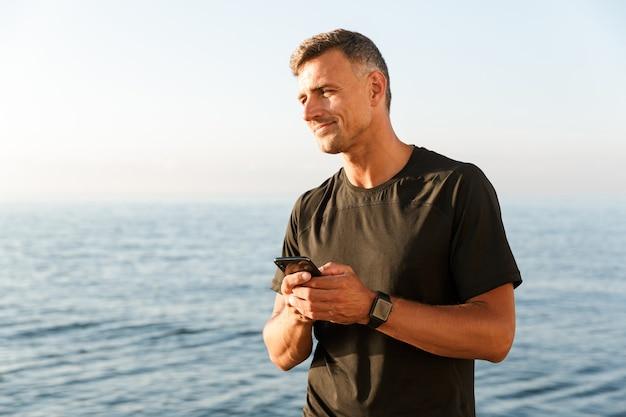 Glimlachende sportman die mobiele telefoon met behulp van