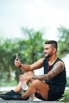 Glimlachende sportman die telefoon in openlucht met behulp van