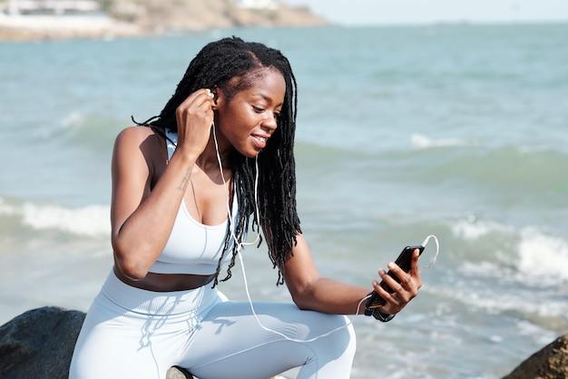 Glimlachende sportvrouw die op een rotsachtig strand zit en oordopjes opdoet tijdens een videogesprek met een vriend of trainer