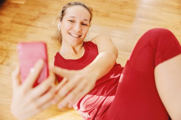 Glimlachende sportvrouw die thuis op de vloer ligt en selfie neemt.