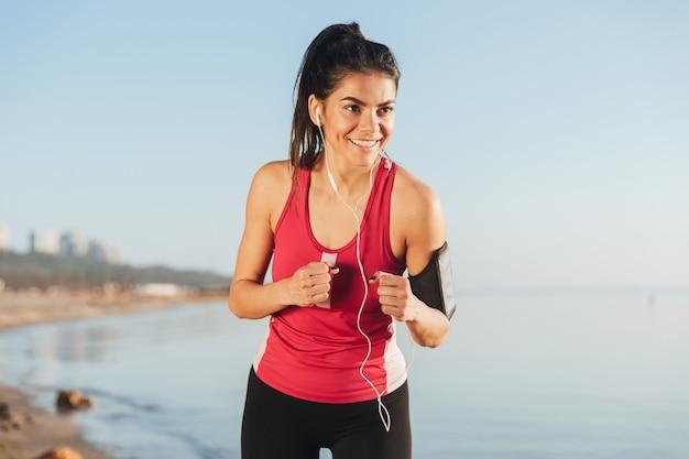 Glimlachende sportvrouw die zich voorbereidt te rennen en wegkijken