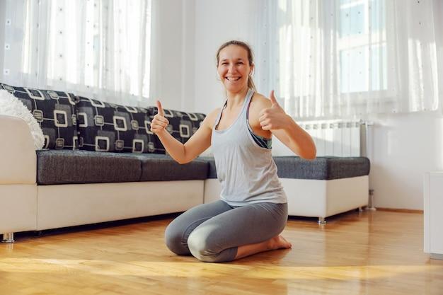 Glimlachende sportvrouw knielend op de vloer thuis en duimen opdagen.