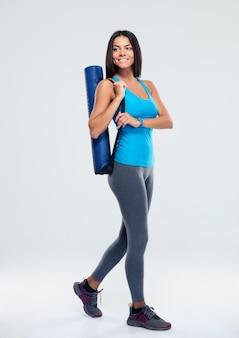 Glimlachende sportvrouw met yogamat het lopen