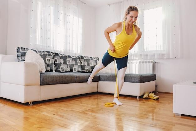 Glimlachende sterke sportvrouw die zich op één been bevindt en machtsrubber uitrekt. ze doet thuis fitnessoefeningen.